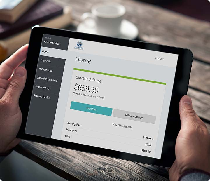 AppFolio screenshot of a rent bill displayed on a tablet that is being held above a wooden table.