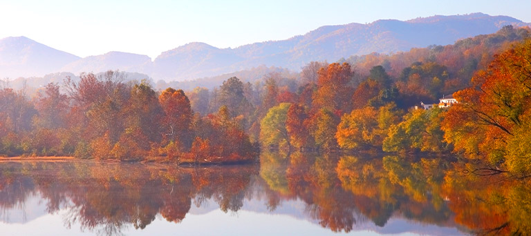 A pond that is reflecting the red, yellow, and orange-leaved trees & mountains that are near it.
